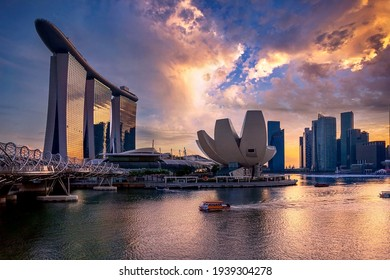 Singapore - December 7, 2013: The Helix bridge, Marina Bay Sands and Art Science museum with downtown in background during sunset. Marina Bay is famous touristic attraction.
