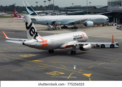 SINGAPORE - DECEMBER 8, 2016: Changi International Airport. Airbus A320 of Jetstar Airways pushes back with a towing truck.