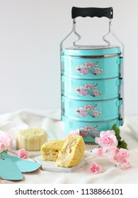 Singapore Durian Moon Cake with Green Peranakan Tiffin. Mooncakes mid-autumn festival, a Chinese festivities for mooncake festival on a white, clean background with pink sakura flowers.