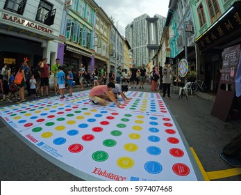 SINGAPORE - Feb 18th, 2017 -  Scenes from a street party in the Tanjong Pagar neighborhood near downtown Singapore. Participants are playing the board game Twister in the street.