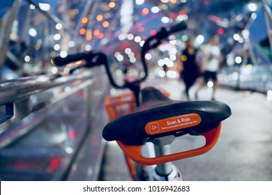 SINGAPORE - FEB 2, 2018: grey and orange bicycle in bike sharing project, scan and ride by mobike parking at city street with blurred light bokeh and couple people at night, singapore