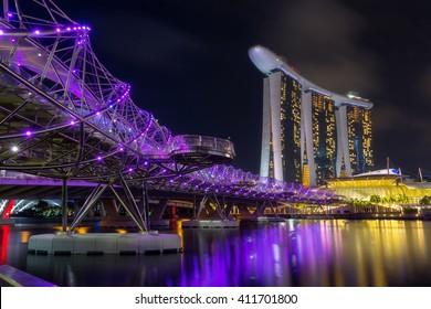 SINGAPORE - FEB 26, 2016: Cityscape of Singapore city skyline with Marina Bay Sands hotel and helix bridge at night in Marina Bay