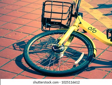 SINGAPORE - FEB 6, 2018: yellow bicycle in bike sharing project, scan to go, ofo, abandon alone in park