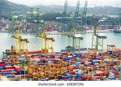 Singapore - February 17, 2017: Amazing view of a container terminal at the Port of Singapore. Ship-to-shore (STS) gantry cranes loading and unloading vessels at shipping yard