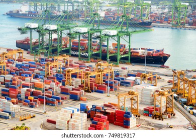 Singapore - February 17, 2017: Container terminal at the Port of Singapore. Cargo ship docked in harbor. Ship-to-shore (STS) gantry cranes loading and unloading vessels at shipping yard.