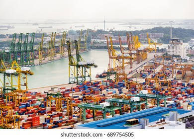 Singapore - February 17, 2017: View of a container terminal at the Port of Singapore. Ship-to-shore (STS) gantry cranes at shipping yard. Sentosa Island and Keppel Harbour are visible in background.