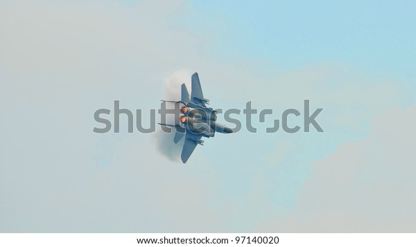 SINGAPORE - FEBRUARY 17: The RSAF F-15SG flying past with a sonic boom and vapour trails during Aerobatic Flying Display at Singapore Airshow on February 17, 2012 in Singapore