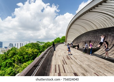 Singapore - February 19, 2017: Tourists taking a picture on the Henderson Waves. Amazing pedestrian wooden bridge curving and leading to a green park. Beautiful sunny cityscape.