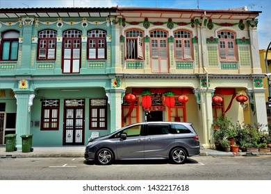 Singapore - February 19 2019: Traditional Peranakan or Straits Chinese shophouses front view with Chinese New Year decorations and silver car in historic Geylang