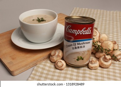 SINGAPORE, SINGAPORE - February 20, 2019: The Campbell Soup Company Cream of mushroom soup can product photography soup with fresh mushrooms. Andy Warhol used Campbell's soup cans in pop art.