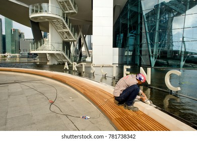 SINGAPORE – february 25, 2011 : finishes and repairs on slabs at the feet of the ArtScience Museum