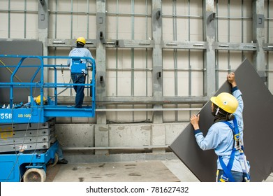 SINGAPORE – february 25, 2011 : workers installing glass plates on a new building