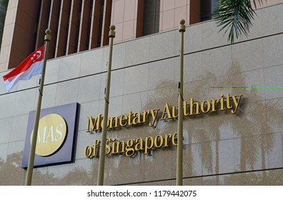 singapore, singapore - february 28, 2018: the front facade of the monetary authority of singapore building with its logo and singapore flag