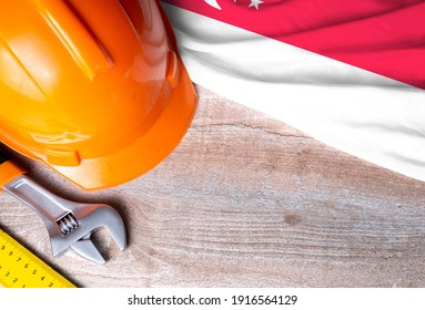 Singapore flag with different construction tools on wood background, with copy space for text. Happy Labor day concept.