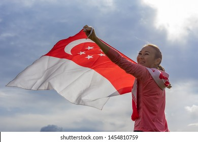 Singapore flag waving on wind on cloudy sky background. Singapore Flag Day. Young joyful woman holds Flag of Singapore fluttering in sunny rays high. Holiday,  National Day of Singapore Concept.