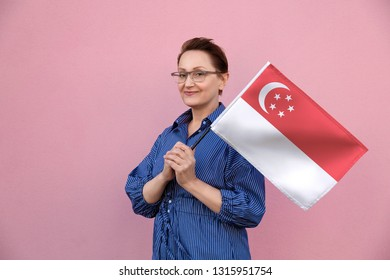 Singapore flag. Woman holding Singapore flag. Nice portrait of middle aged lady 40 50 years old holding a large flag over pink wall background on the street outdoors.