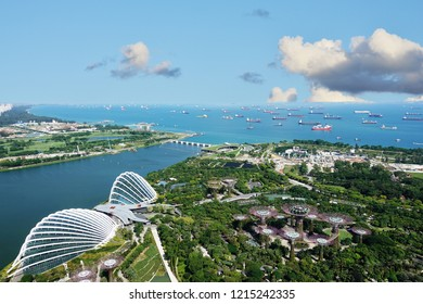 Singapore harbor with many transportation boats and Gardens by the Bay, aerial view from Marina Bay Sand hotel in a sunny day, Singapore, October 15, 2018