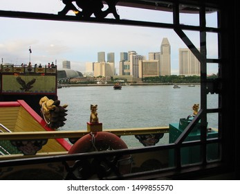 Singapore Harbour, SINGAPORE. 29 Nov 2004. With colourful, carved dragons, the city skyline is framed by the view from a pleasure cruiser in the harbour.