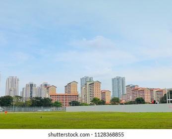 Singapore housing blocks (HDB) across green field under cloudy blue sky