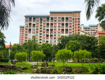 Singapore housing blocks (HDB) across green field with trees and rocks