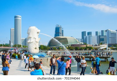 SINGAPORE - JAN 15, 2017: Tourist taking pictures in front of Singapore Merlion fountain. Singapore fountain considered to be a symbol of Singapore.