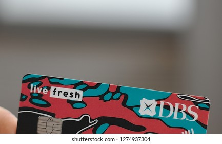 """Singapore, Singapore / Singapore - January 04 2019: Red blue and black DBS Live Fresh Visa credit card design by Mark """"Mr. Sabotage"""" Ong over blurred background"""