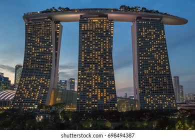 SINGAPORE - JANUARY 12, 2017: View on Marina Bay Sands hotel and Singapore downtown from Skyway bridge in Gardens By The Bay complex after sunset on January 12, 2017