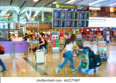 SINGAPORE - JANUARY 13, 2017: Passengers in a hurry near the ,information board in Changi Airport. Changi Airport serves more than 100 airlines operating 6,100 weekly flights