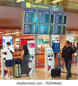 SINGAPORE - JANUARY 13, 2017: Passengers at self check-in kiosk near information board in Changi Airport. Changi Airport serves more than 100 airlines operating 6,100 weekly flights