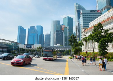 SINGAPORE - JANUARY 15, 2017: People at crosswalk, cars traffic, cityscape with Singapore downtown Core in sunshine