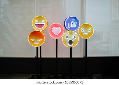 Singapore, January 2018: Neon lit stands of Facebook emojis against a window. The social media giant expanded its popular like button ti include other forms of support such as shock, love and anger.