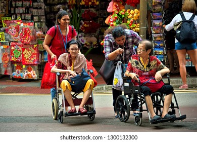 Singapore - January 28 2019: Two elderly Chinese women in wheelchairs with their caregivers on a day out to Chinatown before Chinese New Year.