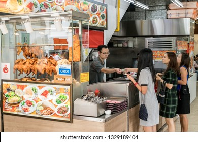 Singapore - January 28, 2019 : - Woman buys traditional roasted duck meal from street food vendors in Singapore