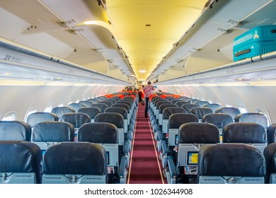 SINGAPORE, SINGAPORE - JANUARY 30, 2018: Indoor view of unidentified people acomodating their luggages in the compartments over the seats inside of Singapore Airline