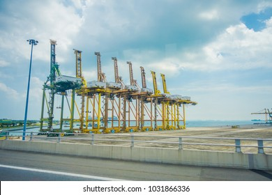 SINGAPORE, SINGAPORE - JANUARY 30, 2018: Outdoor view of some metallic structures at the Port of Singapore. Ship-to-shore STS gantry cranes at shipping yard. Sentosa Island
