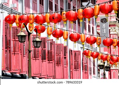 Singapore - January 9 2018: Strings of red Chinese lanterns strung across a street of traditional shop houses to usher in Chinese New Year of the Dog in Singapore, Chinatown