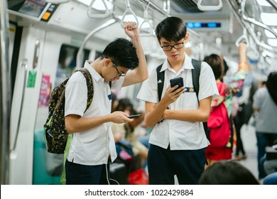 Singapore, January 9, 2018: Two teenager students engrossed in their mobile phones on the MRT train as they commute home from school. Smartphones are increasingly a part of the lives of Singaporeans.
