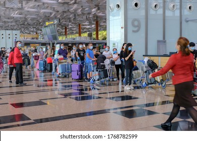Singapore Jul 02 2020 Changi Airport Terminal 3: Travellers returning to their country, wait in line to check in at departure hall. They are wearing face masks; Covid-19 coronavirus outbreak.