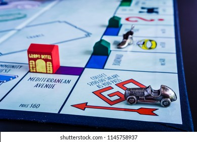 Singapore - Jul 25, 2018:  Monopoly Board Game close up with the car passing the GO. The classic real estate trading game from Parker Brothers was first introduced to America in 1935.