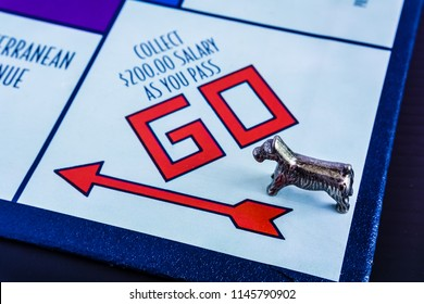 Singapore - Jul 26, 2018:  Monopoly Board Game close up with the dog token passing the GO. The classic real estate trading game from Parker Brothers was first introduced to America in 1935.