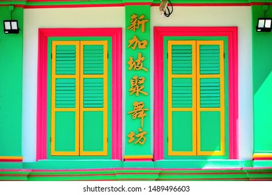 Singapore - July 12 2019: Front view of traditional Singapore shophouse with colourful wooden shutters and golden Chinese characters in historic Bugis district