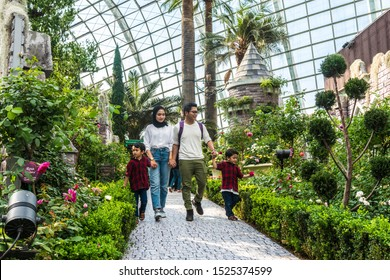 Singapore - July 12th 2019 : Asian Malay muslim family with two male children enjoying time together in Garden By The Bay Flower Dome, Singapore. Pathway in garden during daytime.