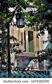 Singapore - July 2 2019: Old window with antique  wooden shutters on Singapore shop house framed by dark shadows of trees in soft morning light in historic Telok Ayer, Singapore in portrait view