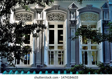 Singapore - July 2 2019: Old windows with antique  wooden shutters on Singapore shop house framed by dark shadows of trees in soft morning light in historic Telok Ayer, Singapore.