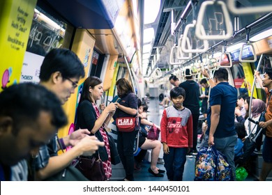 SINGAPORE - JULY, 2018: Mixture of commuters on a singapore MRT train, on their mobile phones oblivious to the lone boy finding his way.