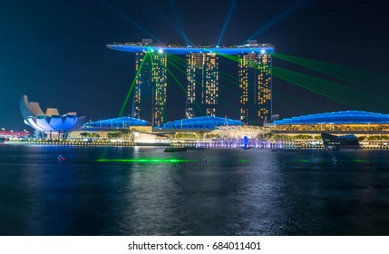 Singapore, Singapore - July 25, 2017: The famous Marina Bay Sands hotel during its light show with its lights reflecting on the Singapore river in the marina in Singapore at night.
