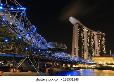 SINGAPORE - JULY 27: Helix Bridge and Marina Bay Sands on July 27, 2012. At night, the Helix Bridge is illuminated by a series of lights creating a special visual experience for the visitors.