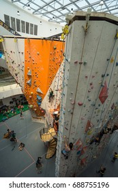 Singapore, Singapore - July 29, 2017: Woman and men are climbing on rock climbing wall in sportswear and equipment at Stadium Singapore