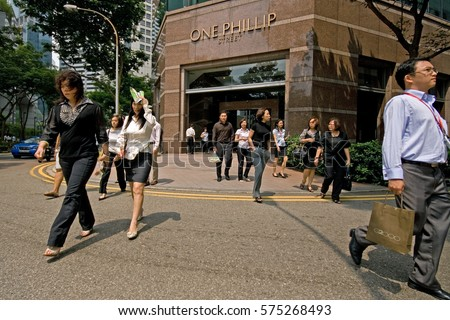 SINGAPORE - JULY 6, 2009: Business people crossing a street at the Central Business District (CBD) in Singapore.