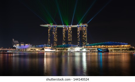 SINGAPORE - JUN 1: Laser show on Marina Bay Sands complex skyline at night on Jun 1, 2013 in Singapore. It is an integrated resort became a  symbol of modern Singapore.